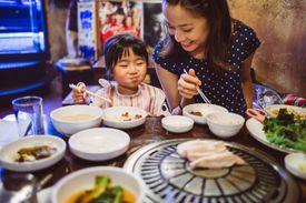 Mom & child having meal in Korean restaurant