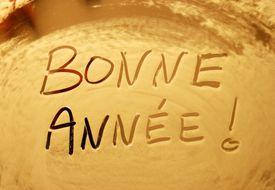 Happy new year in French written in shaving foam on a mirror.