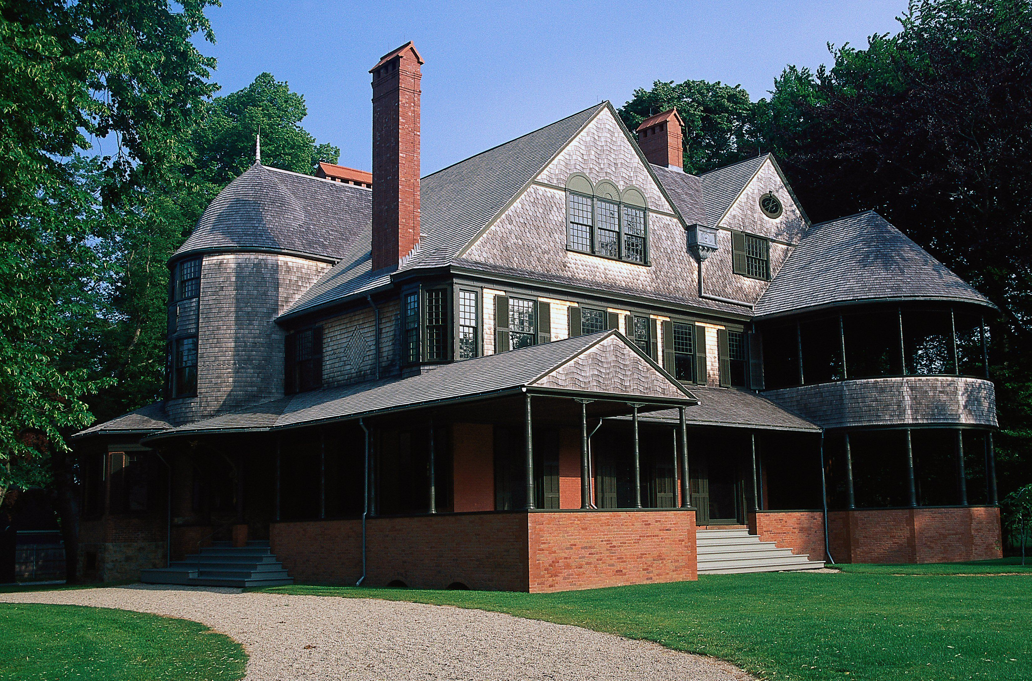 large 2 1/2 story home with wood shingles on the top of a brick first floor, with gables and turret porches and multiple chimneys