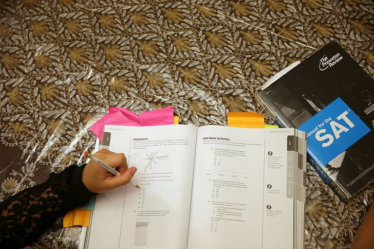 A student uses books to study for the SAT