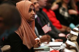 Woman wearing hijab listens to a speech being given at a naturalization ceremony with her hands folded over citizenship documents