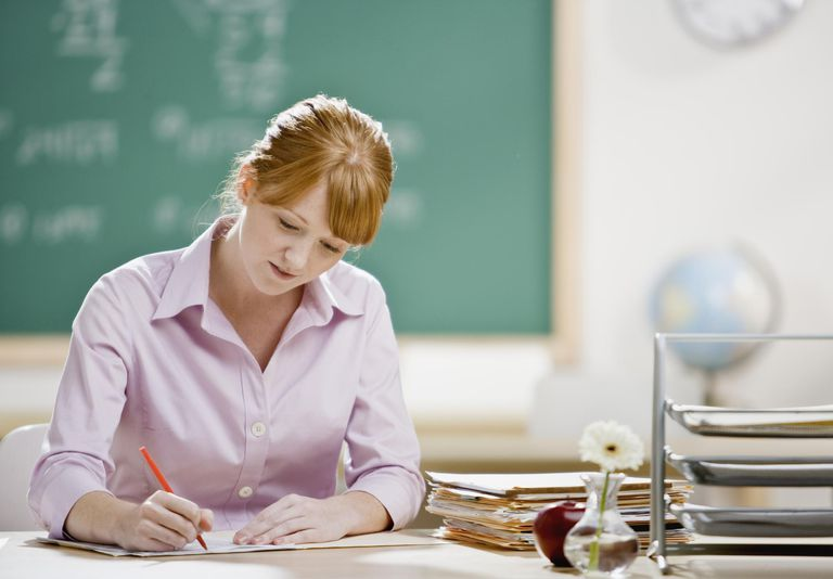 Young teacher sitting in classroom, writing