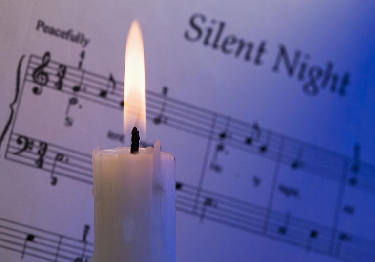 a lit candle in front of silent night sheet