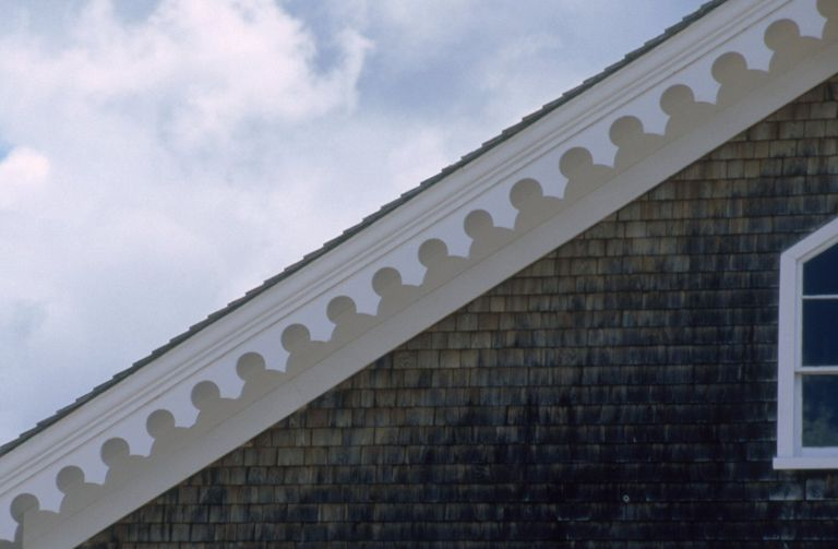 scallopped trim along the roofline of a shingled home