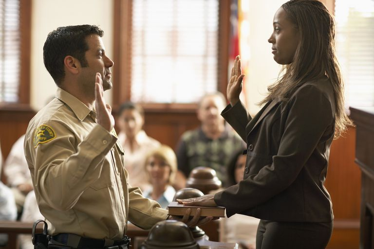 woman swearing on the Bible in a courtroom