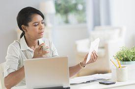 Mujer con sobre en mano delante de computadora