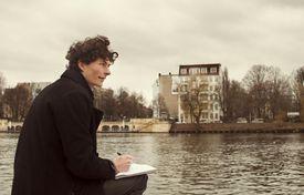 Man Writing in Journal by River in Berlin