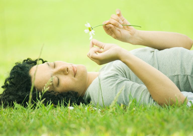 woman laying in grass pulling flower petals