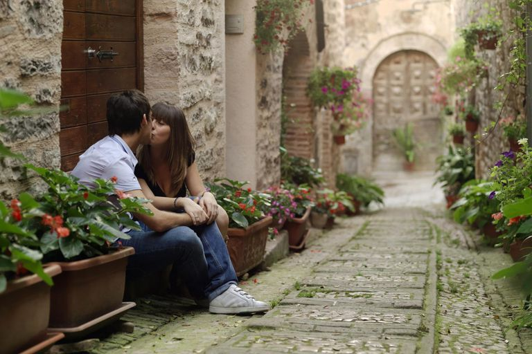 A young couple kissing in a flowered alleyway.