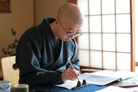 Man doing calligraphy in Japanese-style room
