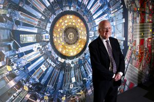 Professor Peter Higgs stands in front of an image of the Large Hadron Collider