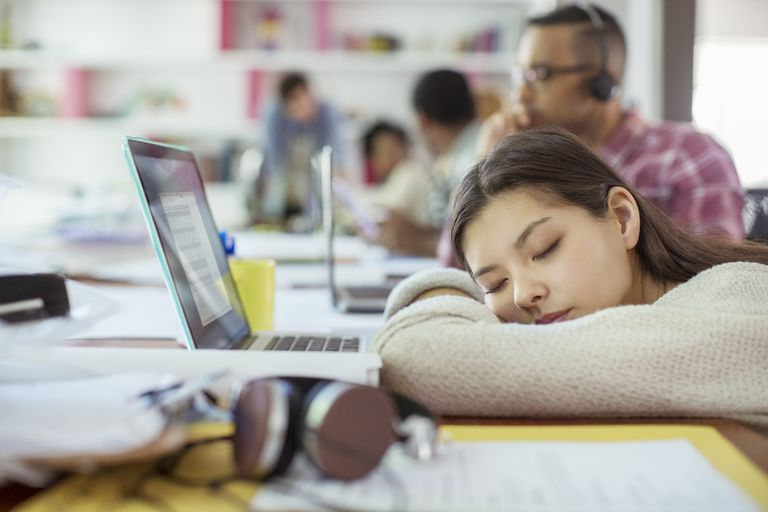 student sleeping by laptop