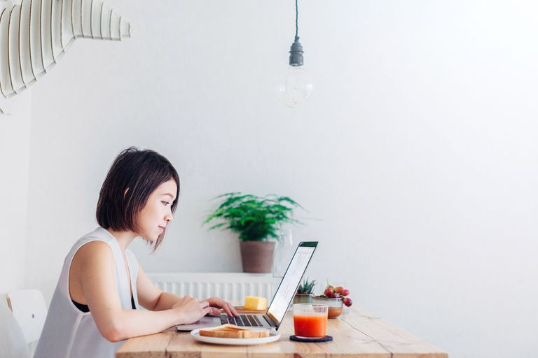 Woman working on computer at breakfast