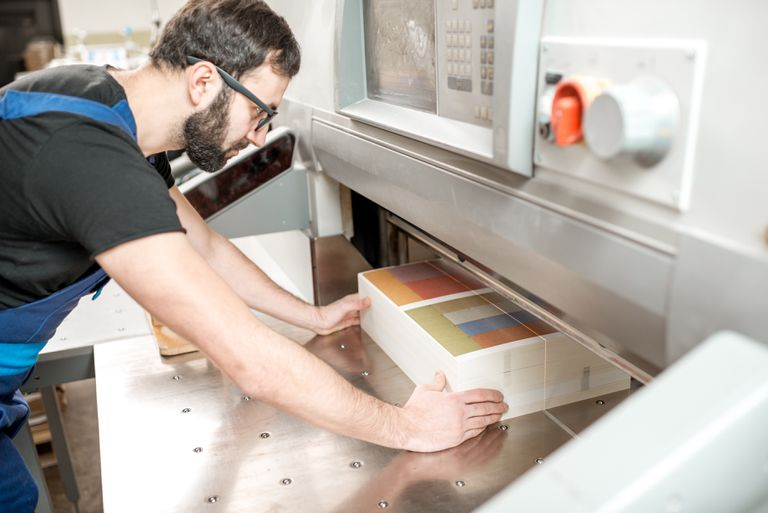 Man lining up paper in printing press