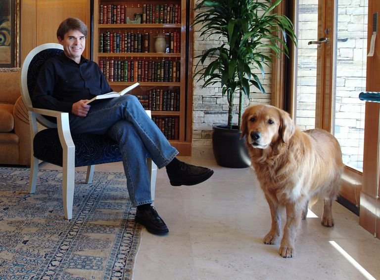 Dean Koontz in a chair with a book in his lap next to his dog