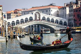 Two Italian gondolas on a waterway in Venice on a sunny day.