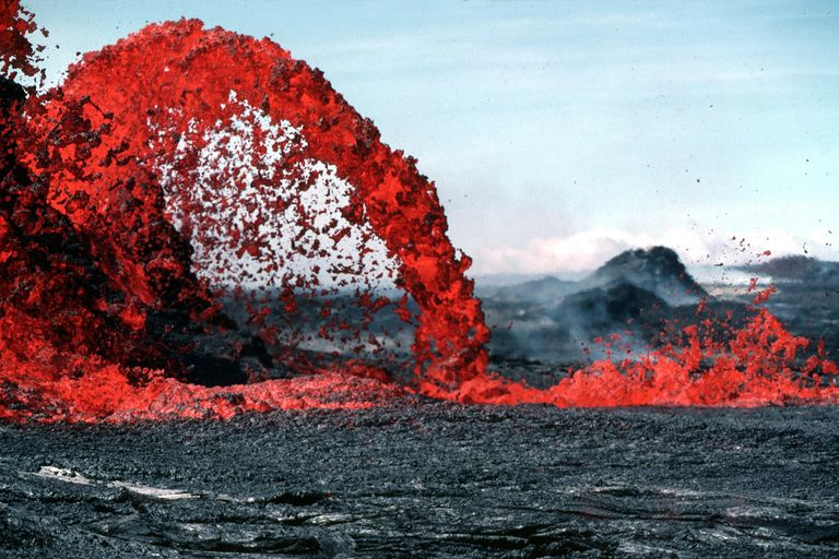Lava flowing across rocky ground.