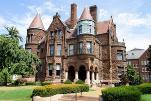 Large Romesque Revival home with red rusticated stone, turrets, gables, and arches