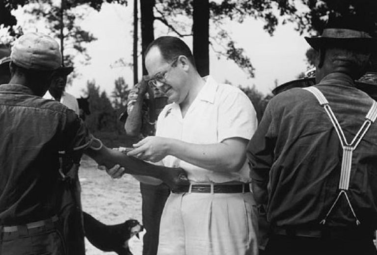 Black and white photograph of a man taking samples for the Tuskegee study.