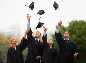 Four graduates toss their caps in the air