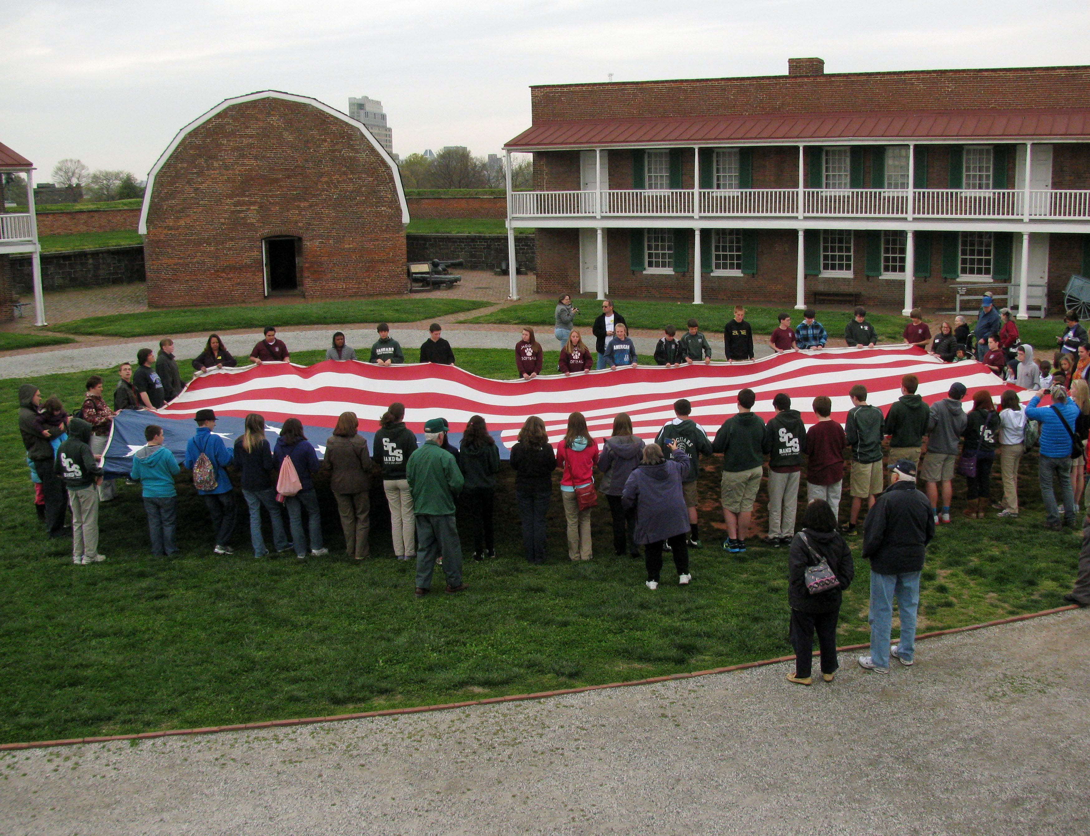 A full-size replica of the Fort McHenry flag unrolled at the parade ground.