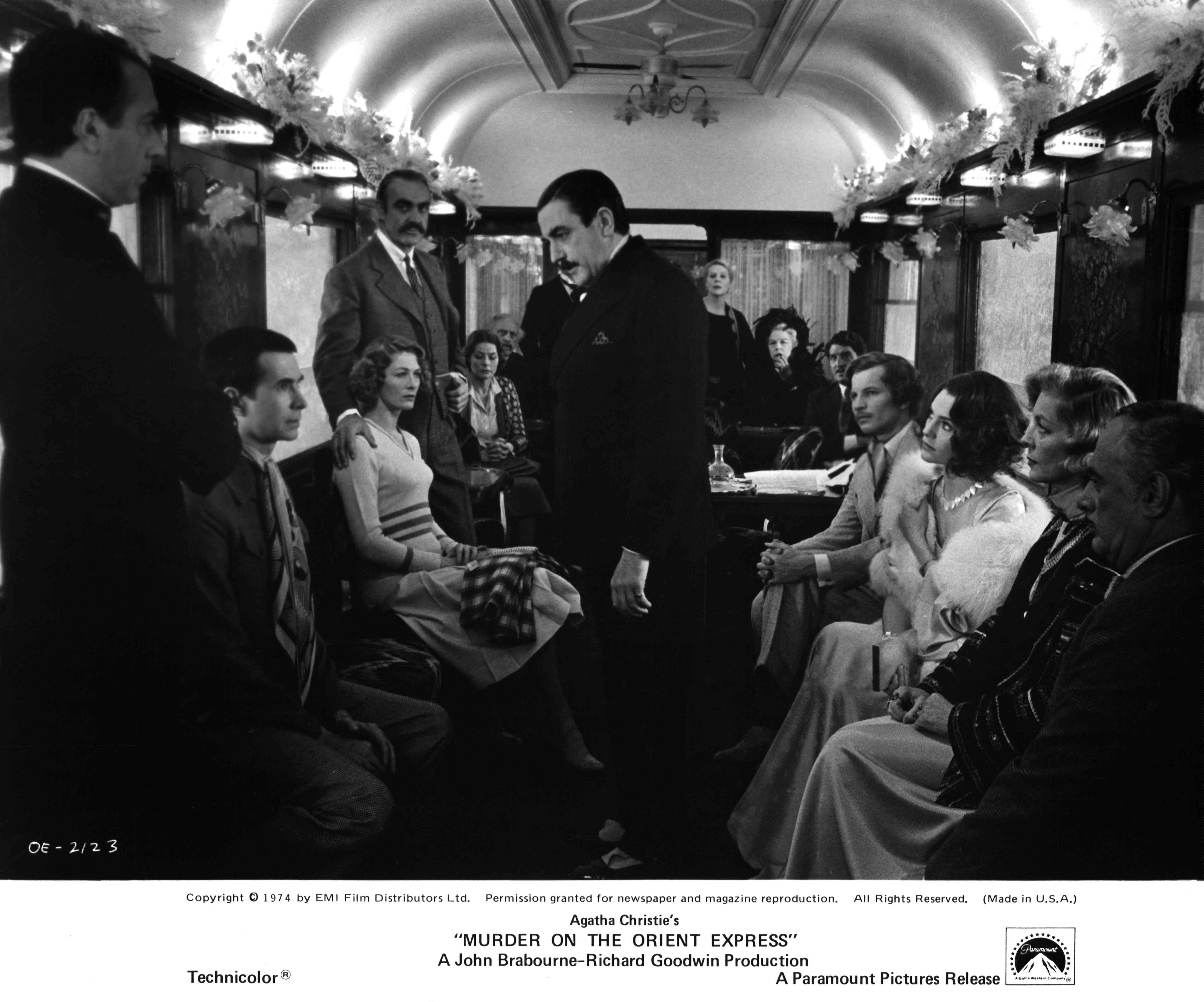 A group of well-dressed people sitting on a train