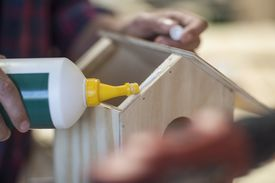 Man working with glue on birdhouse