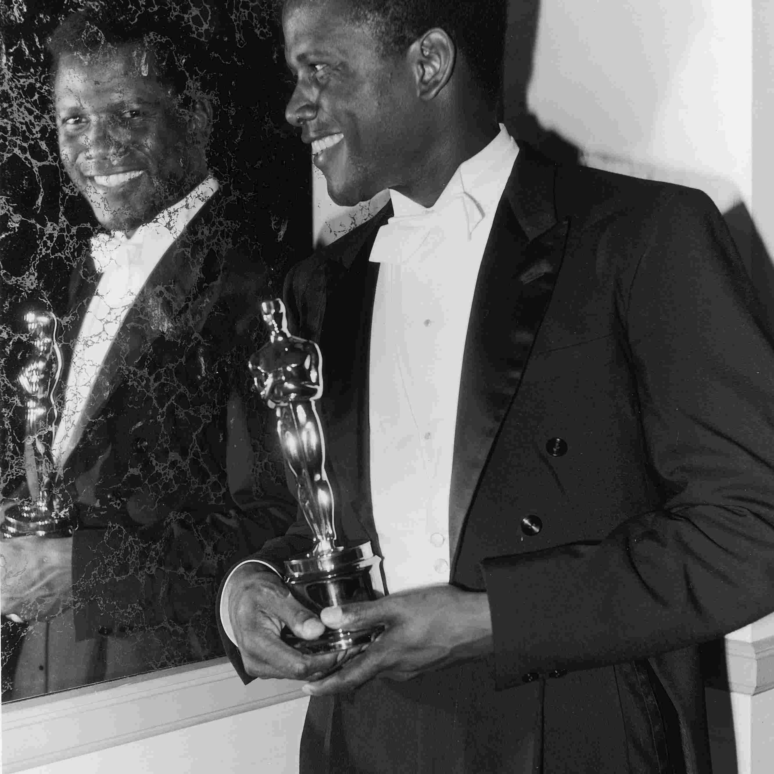 Sidney Poitier, holding Oscar and looking in mirror backstage at the Academy Awards, 1964