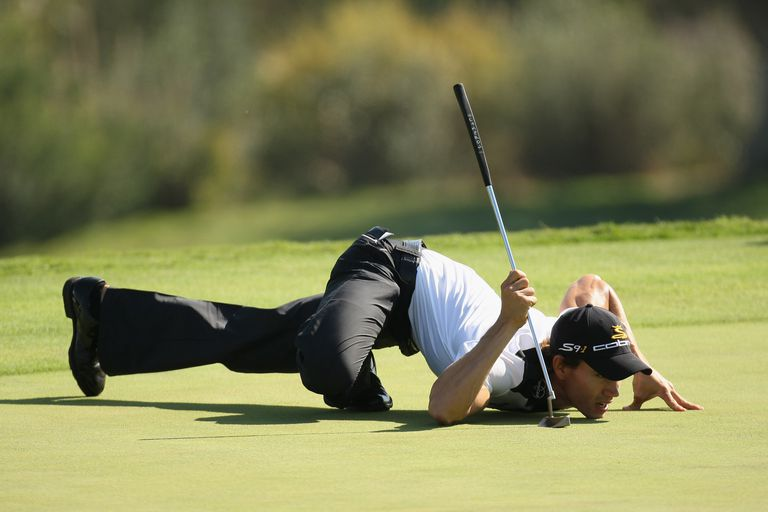 Camilo Villegas crouches close to the ground to line up a putt in a PGA Tour tournament.