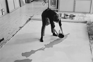 Helen Frankenthaler pouring paint carefully onto a canvas on the floor.