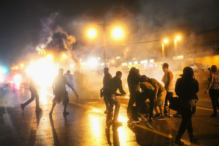 Police fire tear gas at demonstrators protesting the shooting of Michael Brown on August 17, 2014 in Ferguson, Missouri.