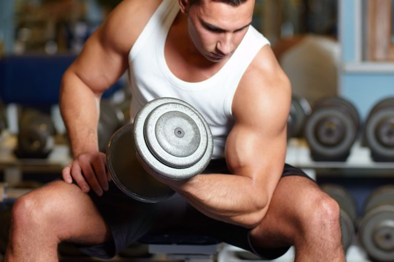Man in tank top lifting weight at gym.