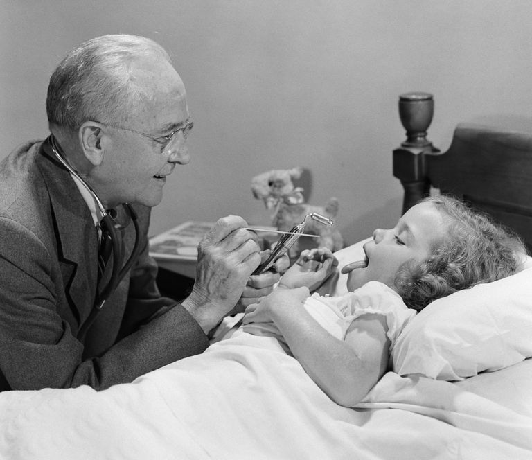 1950s photo of a doctor examining a sick girl