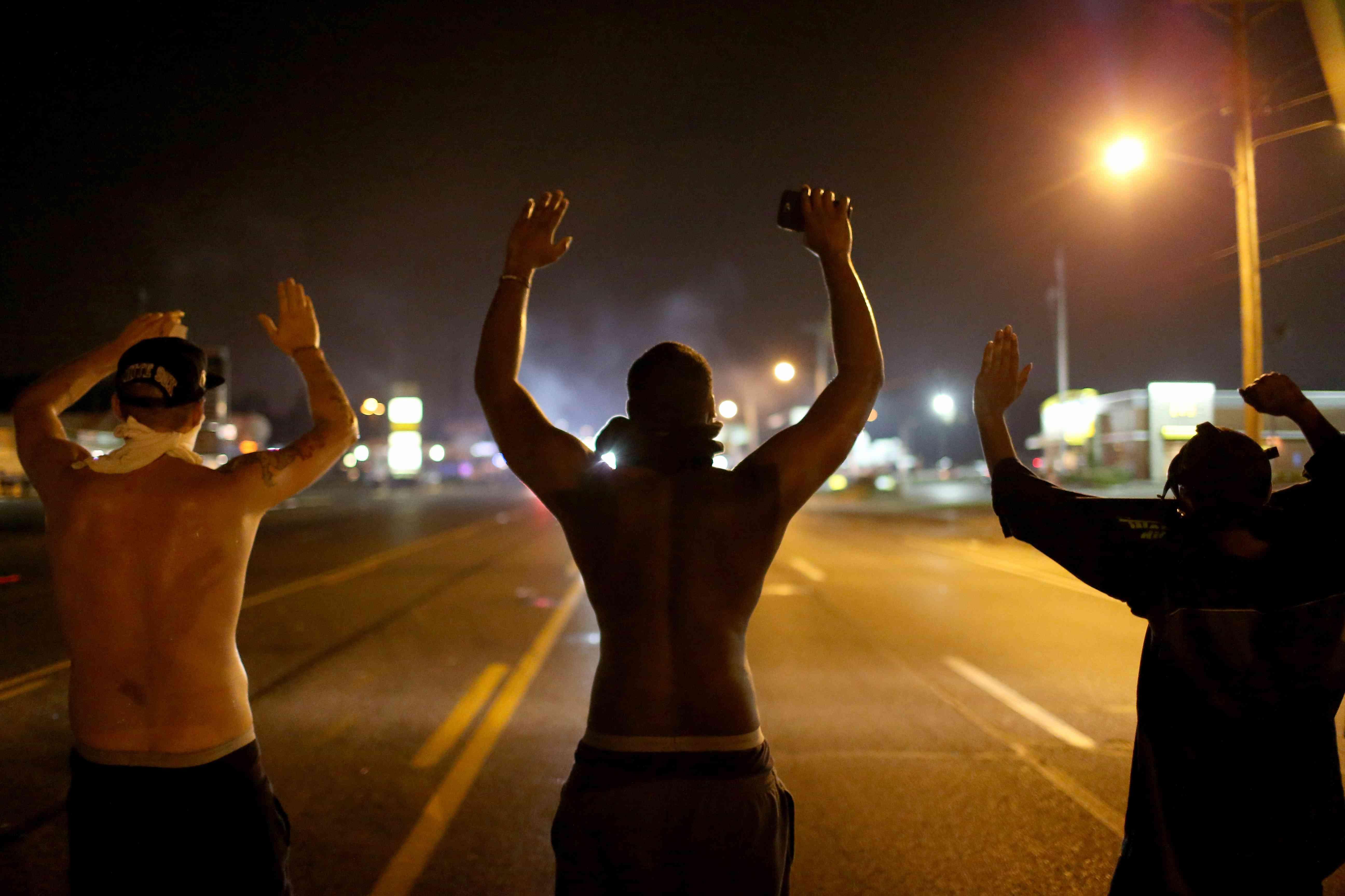 """Demonstranten heben ihre Arme und singen """"Hände hoch, nicht schießen"""", während sie gegen den Tod von Michael Brown am 17. August 2014 in Ferguson, Missouri, protestieren."""