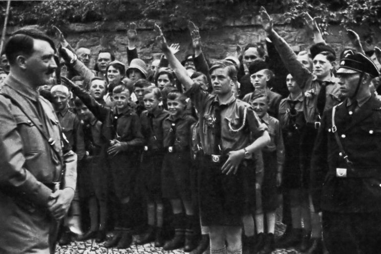 1933: Nazi leader Adolf Hitler smiles while uniformed Saxon youths salute him outdoors in Erfurt, Germany.