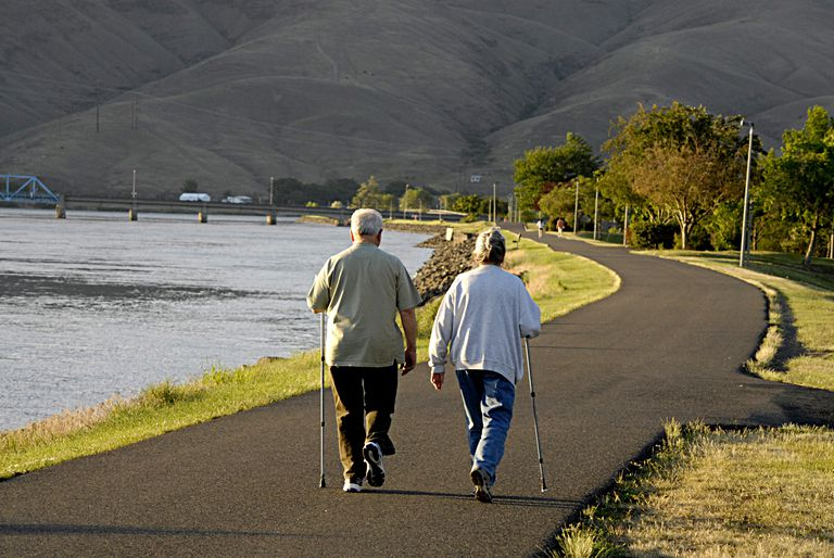 Two elderly people walking a path along a river, nearly 30 miles of recreational landscape