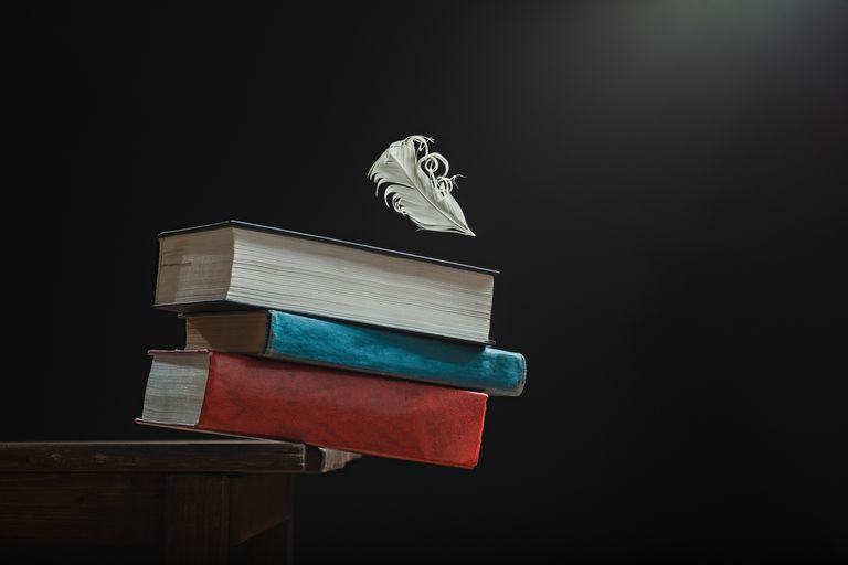 A stack of books balancing on the edge of the table and a feather dropping on them threatening to upset the delicate balance. Conceptual photo