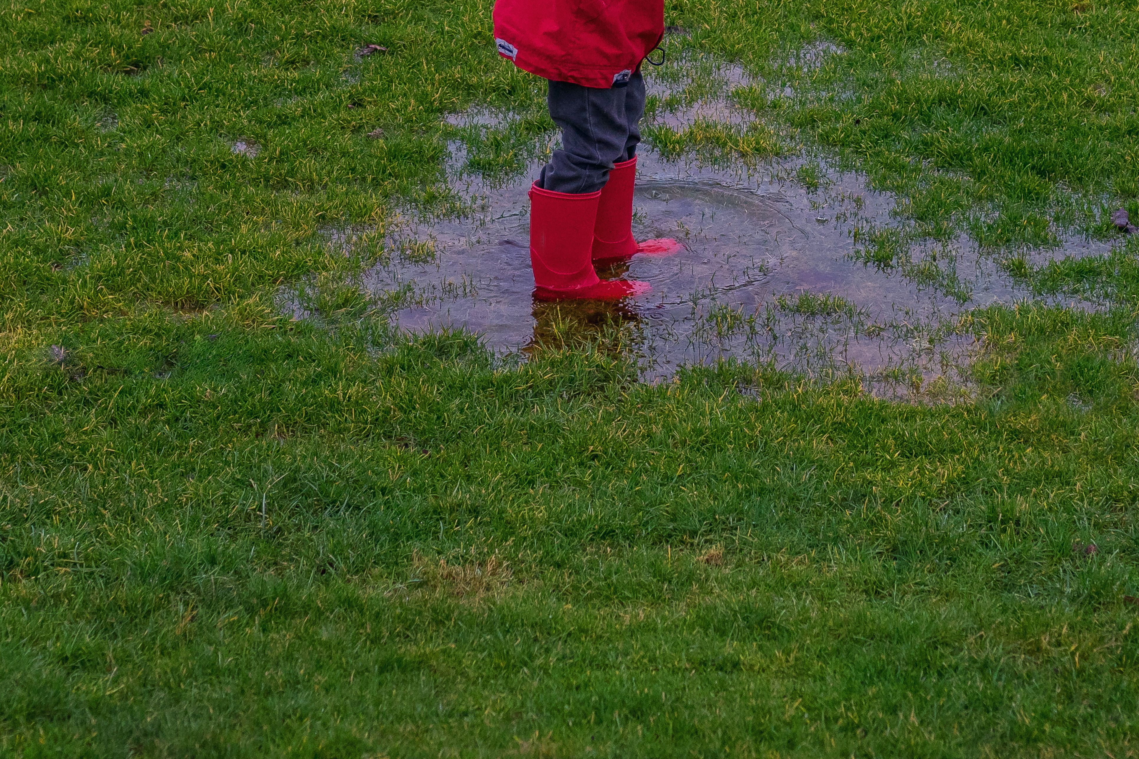 Low section of a boy standing in a puddle