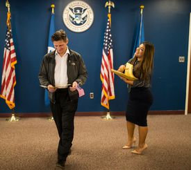 man receiving his green card from the U.S. government
