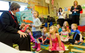 Teacher reading out loud to students in a classroom.