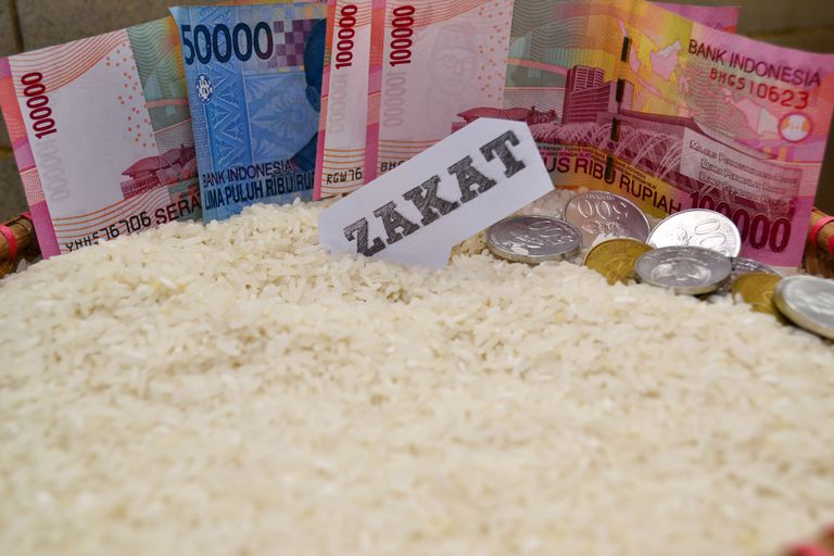 Indonesian money and rice as alms or zakat for muslim