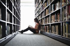 College student reading a book in library stacks
