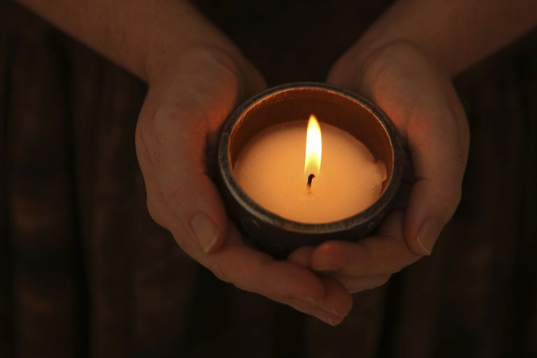 Hands with a lit candle