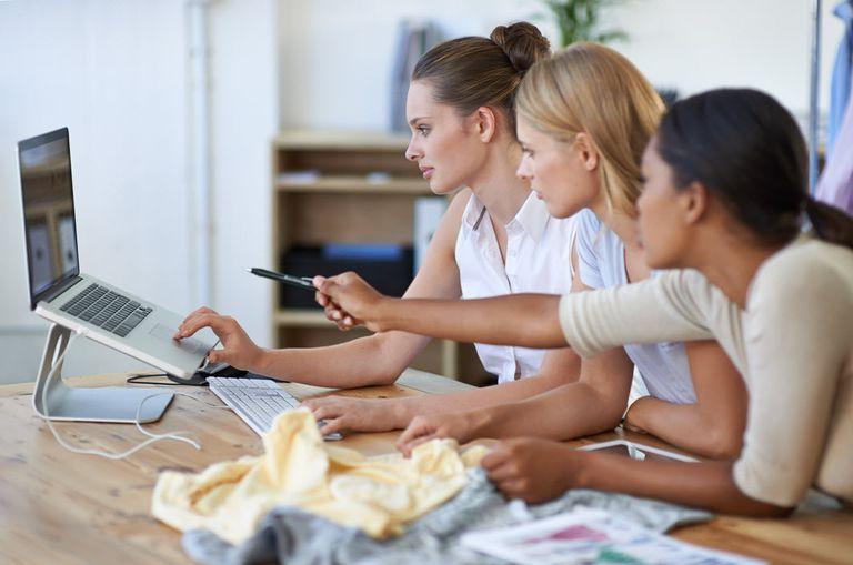 Three women reviewing website design on laptop