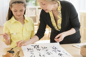 Grandmother and granddaughter painting Japanese symbols
