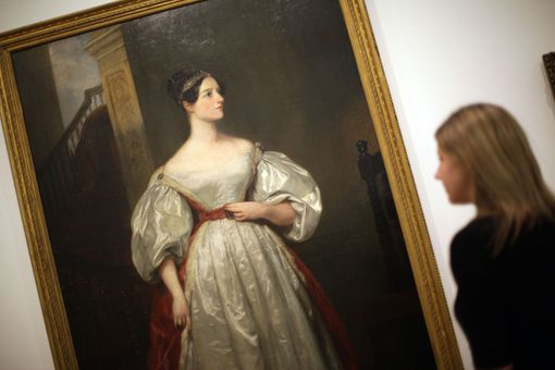 A gallery employee looks at a painting of Ada Lovelace, mathematician and daughter of Lord Byron.