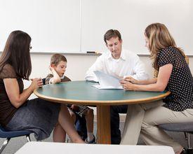 A teacher, a child, and his parents attend a parent teacher conference