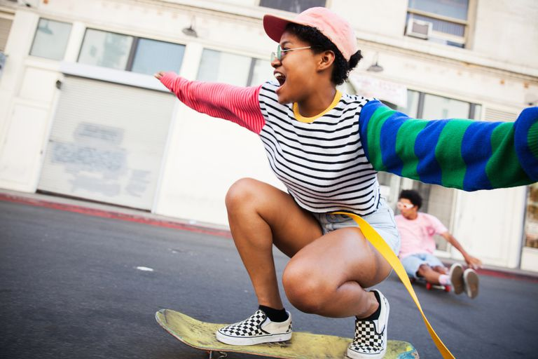 Young woman skateboarding with friend in background