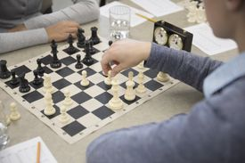 Close up middle school students playing chess in chess club