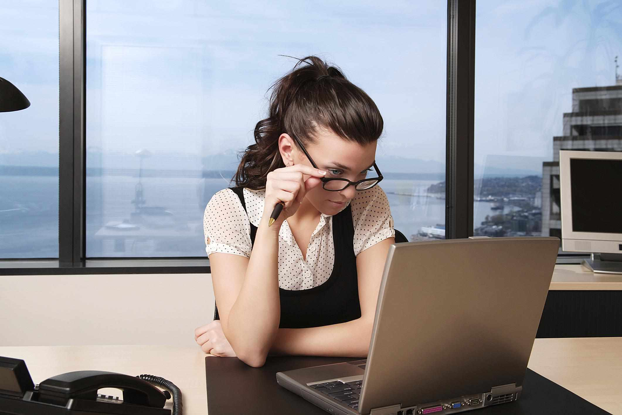 A woman looks over her glasses at her laptop screen